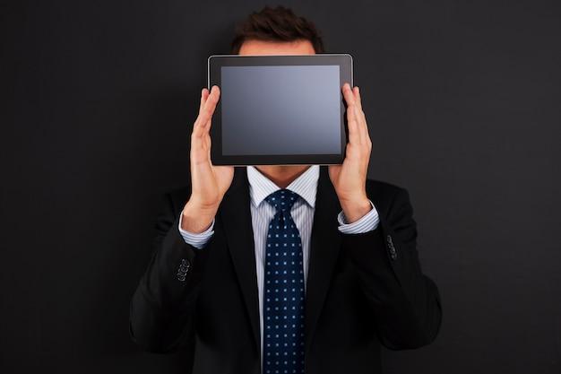 Geschäftsmann, der digitales tablett vor seinem gesicht hält
