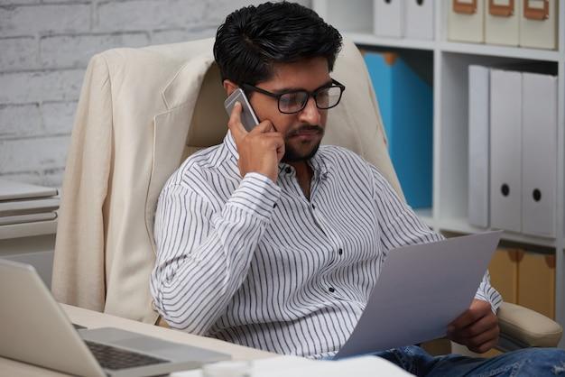 Geschäftsmann, der dokument am telefon bespricht