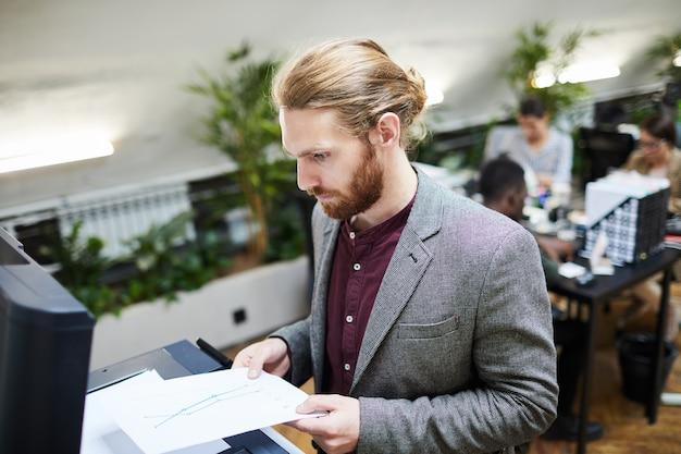 Geschäftsmann, der dokumente im büro scannt