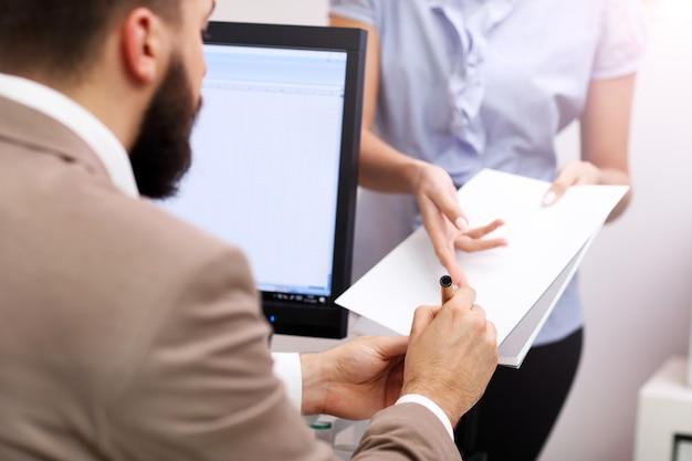 Geschäftsmann, der dokumente im büro unterschreibt