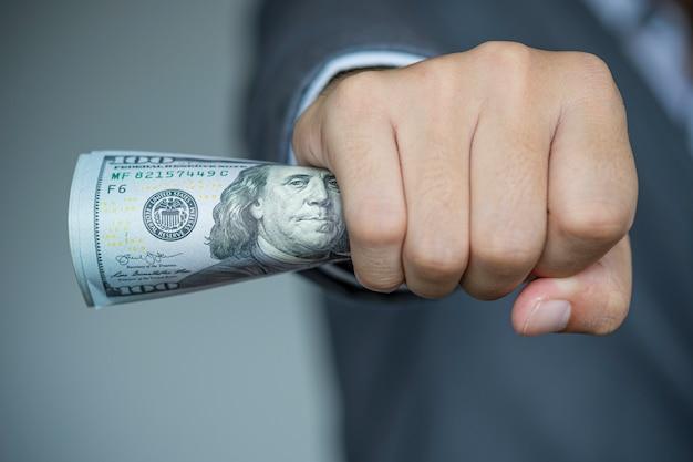 Geschäftsmann, der dollarbanknote hält