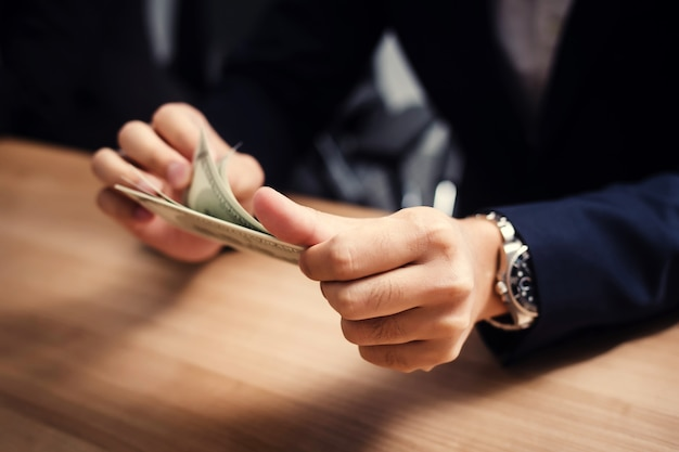 Geschäftsmann, der dollarbanknoten im konferenzzimmer zählt