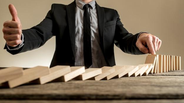 Geschäftsmann, der dominosteinreihe vom zerbröckeln stoppt
