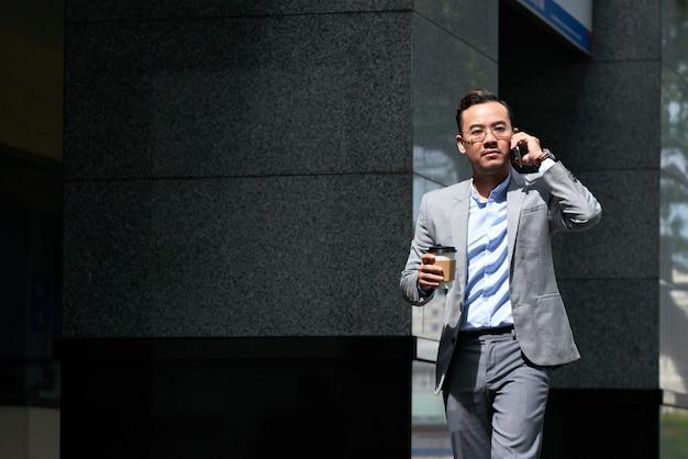 Geschäftsmann, der draußen einen telefonanruf in bewegung macht