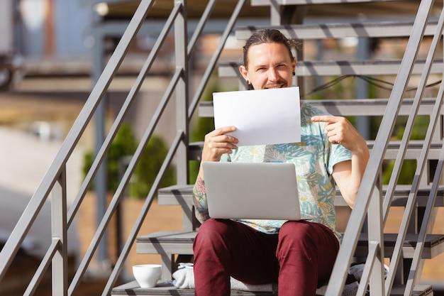 Geschäftsmann, der draußen mit laptop arbeitet, leeres papier hält