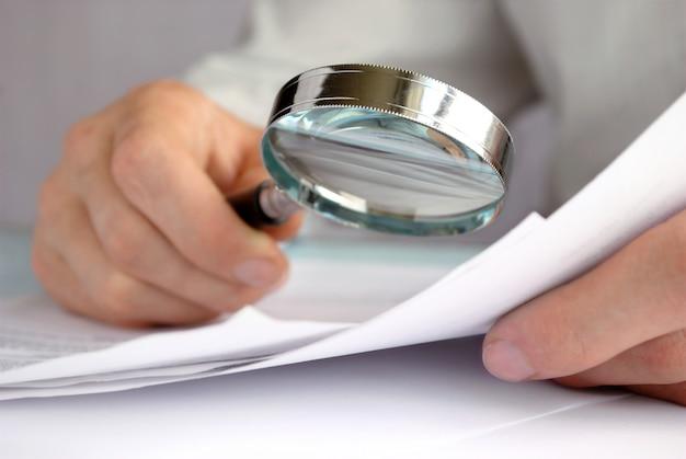 Geschäftsmann, der durch eine lupe zu den dokumenten schaut