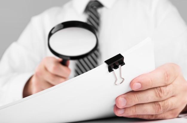 Geschäftsmann, der durch eine lupe zu dokumenten schaut