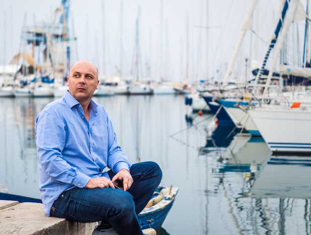 Geschäftsmann, der durch teure segelboote und yachten in einer küstenstadt sitzt