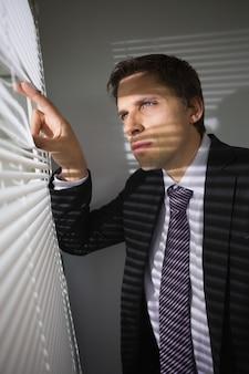Geschäftsmann, der durch vorhänge im büro späht