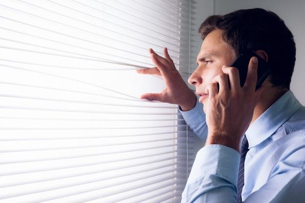 Geschäftsmann, der durch vorhänge während beim anruf im büro späht
