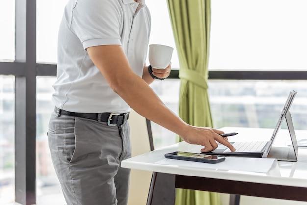 Geschäftsmann, der e-mails auf dem laptop überprüft und eine tasse kaffee hält