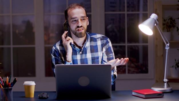 Geschäftsmann, der ein argumentgespräch über das telefon führt, während er nachts in seinem heimbüro arbeitet.