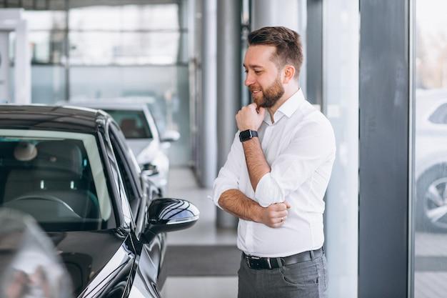 Geschäftsmann, der ein auto in einem ausstellungsraum kauft