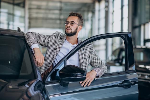 Geschäftsmann, der ein auto in einem autoausstellungsraum wählt