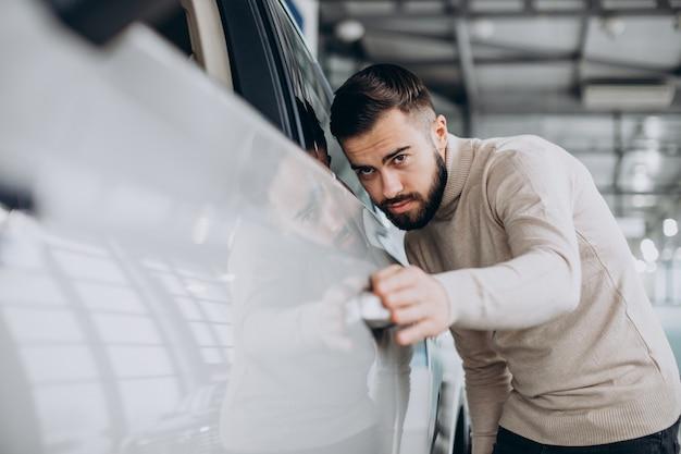 Geschäftsmann, der ein auto in einem autosalon wählt