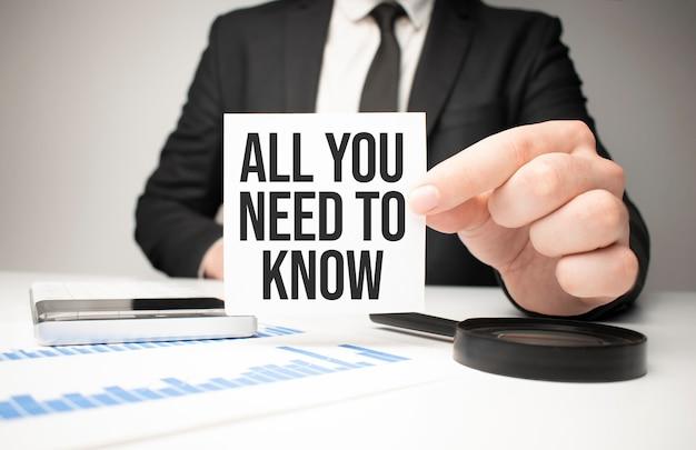 Geschäftsmann, der ein blatt papier mit einer nachricht hält alles, was sie wissen müssen