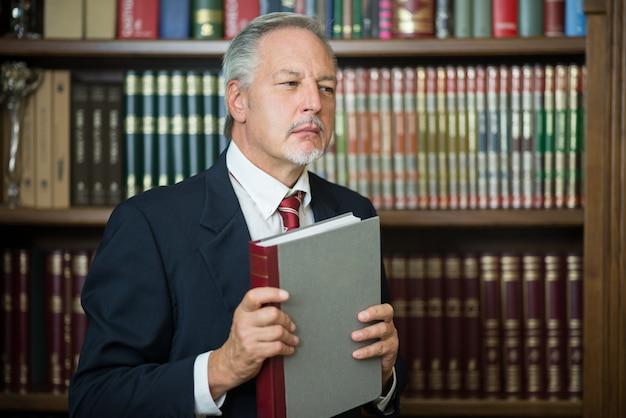 Geschäftsmann, der ein buch in einer bibliothek hält
