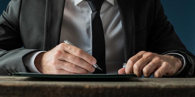 Geschäftsmann, der ein dokument unterschreibt