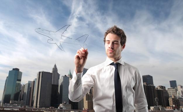 Geschäftsmann, der ein flugzeug zeichnet