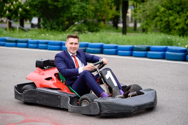 Geschäftsmann, der ein kinderfahrzeug fährt.
