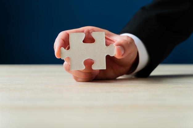 Geschäftsmann, der ein leeres puzzleteil hält und es der kamera zeigt.