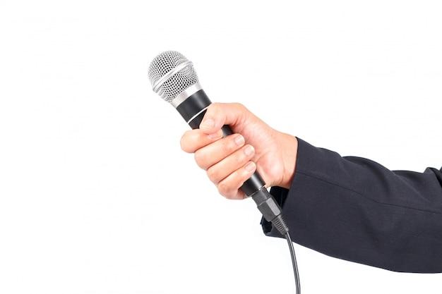 Geschäftsmann, der ein mikrofon lokalisiert auf weißem hintergrund hält