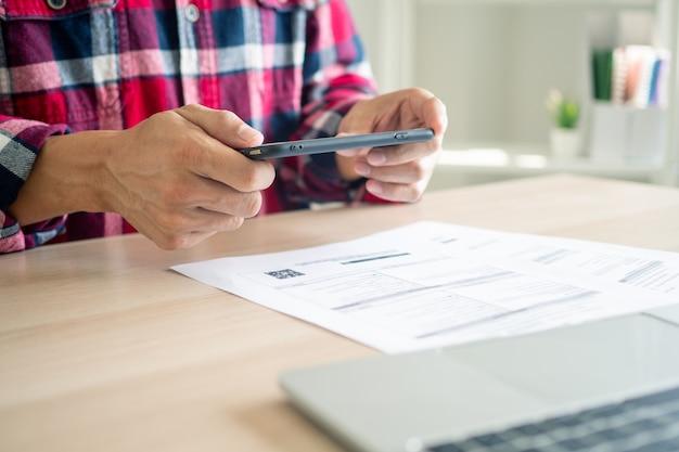 Geschäftsmann, der ein mobiltelefon verwendet, um rechnungen unter verwendung von mobiltelefonanwendungen zu bezahlen.
