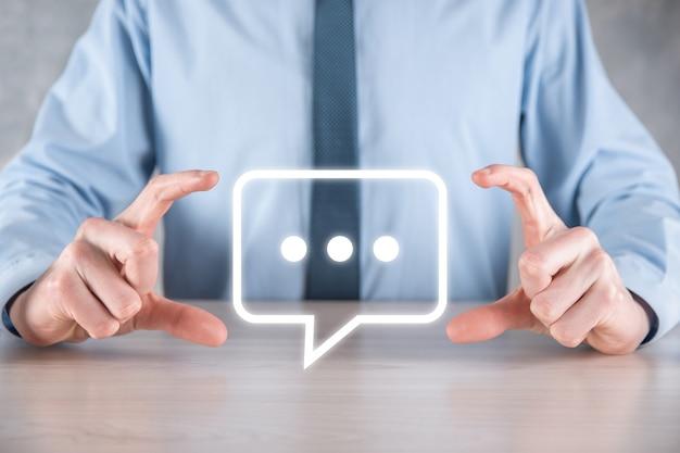Geschäftsmann, der ein nachrichtensymbol hält, blase-talk-benachrichtigungszeichen in seinen händen. chat-symbol, sms-symbol, kommentarsymbol, sprechblasen