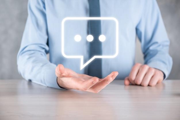 Geschäftsmann, der ein nachrichtensymbol hält, blase-talk-benachrichtigungszeichen in seinen händen. chat-symbol, sms-symbol, kommentarsymbol, sprechblasen.