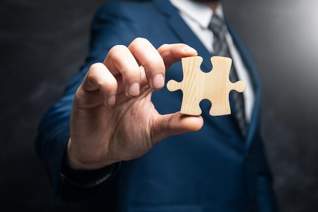Geschäftsmann, der ein puzzleteil in seiner hand auf einer schwarzen oberfläche hält