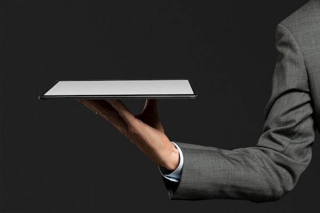 Geschäftsmann, der ein unsichtbares hologramm präsentiert, das von der fortschrittlichen technologie des tablets projiziert wird