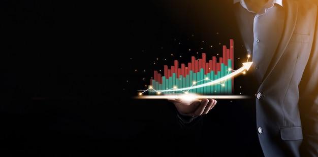Geschäftsmann, der ein wachsendes virtuelles hologramm von statistik, grafik und diagramm mit pfeil oben auf dunklem hintergrund hält und zeigt. aktienmarkt. geschäftswachstum, planung und strategiekonzept.