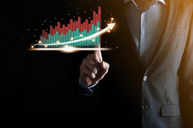 Geschäftsmann, der ein wachsendes virtuelles hologramm von statistik, grafik und diagramm mit pfeil oben auf dunkler wand hält und zeigt. aktienmarkt. geschäftswachstum, planung und strategiekonzept.