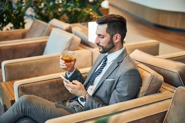 Geschäftsmann, der ein whiskyglas anhebt und sein handy benutzt