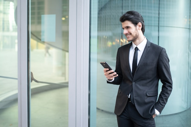 Geschäftsmann, der eine app auf seinem smartphone in einer geschäftsumgebung verwendet