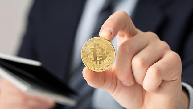 Geschäftsmann, der eine bitcoin-nahaufnahme hält