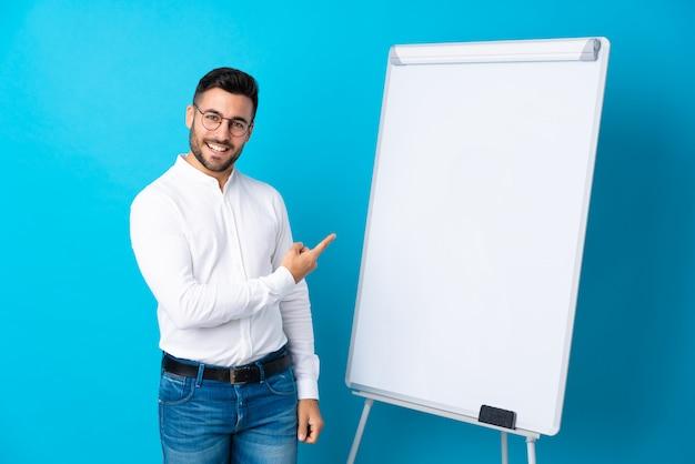 Geschäftsmann, der eine darstellung auf dem weißen brett gibt eine darstellung auf weißem brett gibt und auf die seite zeigt