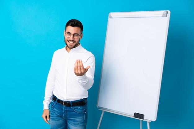 Geschäftsmann, der eine darstellung auf dem weißen brett gibt eine darstellung auf weißem brett gibt und einlädt, mit der hand zu kommen