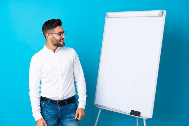 Geschäftsmann, der eine darstellung auf dem weißen brett gibt eine darstellung auf weißem brett gibt und seite schaut