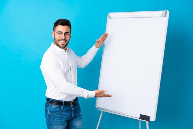 Geschäftsmann, der eine darstellung auf dem weißen brett gibt eine darstellung auf weißem brett gibt