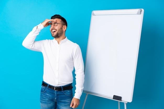 Geschäftsmann, der eine darstellung auf dem weißen brett gibt eine darstellung auf weißem brett und beim beabsichtigen der lösung gibt