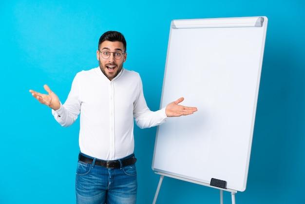 Geschäftsmann, der eine darstellung auf dem weißen brett gibt eine darstellung auf weißem brett und mit entsetztem ausdruck gibt