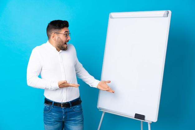 Geschäftsmann, der eine darstellung auf dem weißen brett gibt eine darstellung auf weißem brett und mit überraschungsausdruck gibt