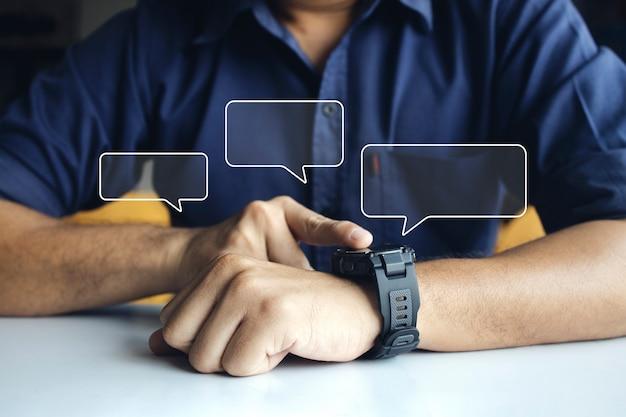Geschäftsmann, der eine digitale smartwatch in der hand trägt, die den bildschirm berührt, um die benachrichtigung zu öffnen, die nachricht und den aktivitätstracker im handgelenk zu lesen