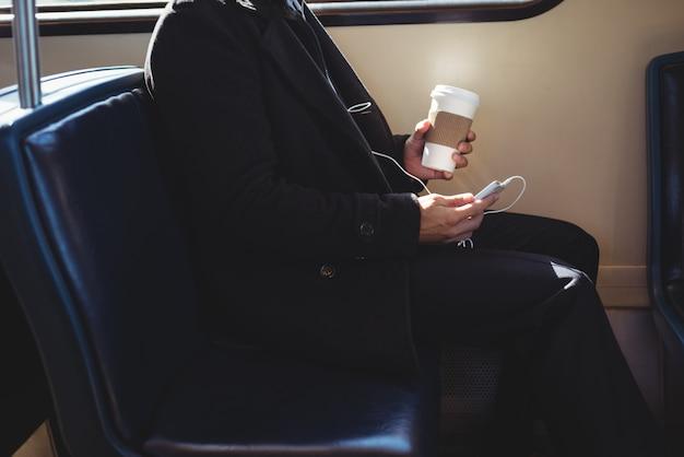 Geschäftsmann, der eine einwegkaffeetasse hält und handy verwendet