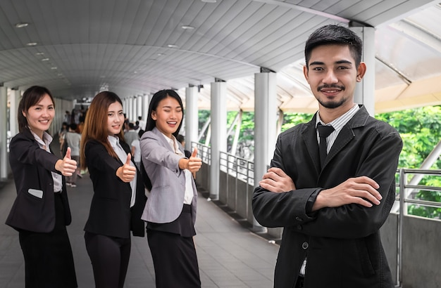 Geschäftsmann, der eine erfolgreiche unternehmensgruppe mit den daumen oben führt