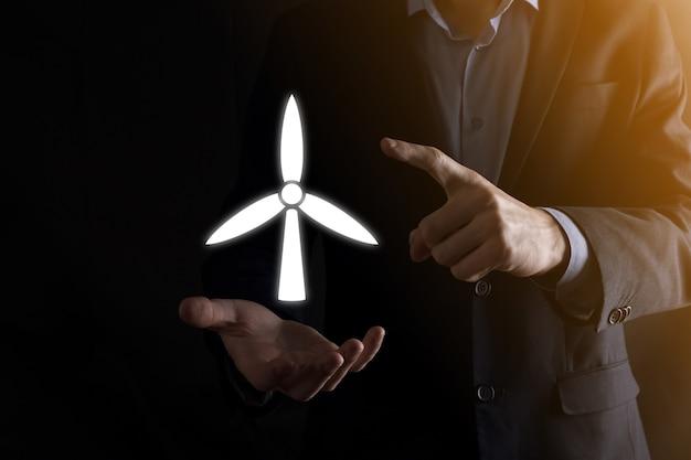 Geschäftsmann, der eine ikone einer windmühle hält, die umweltenergie produziert. dunkler hintergrund.