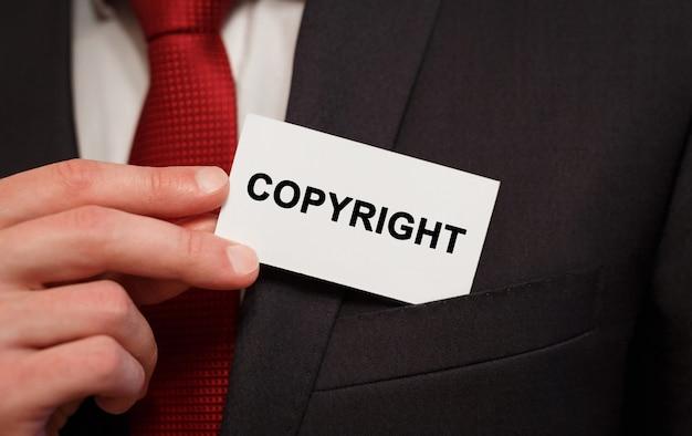 Geschäftsmann, der eine karte mit text copyright in die tasche steckt