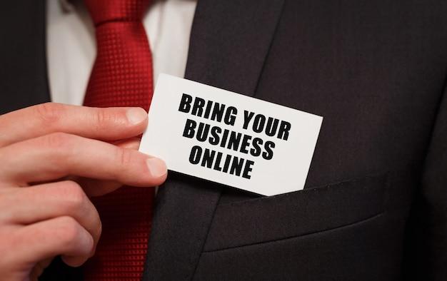 Geschäftsmann, der eine karte mit text einbringt bringen sie ihr geschäft online in die tasche