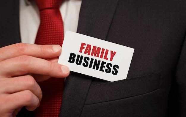 Geschäftsmann, der eine karte mit text family business in die tasche steckt